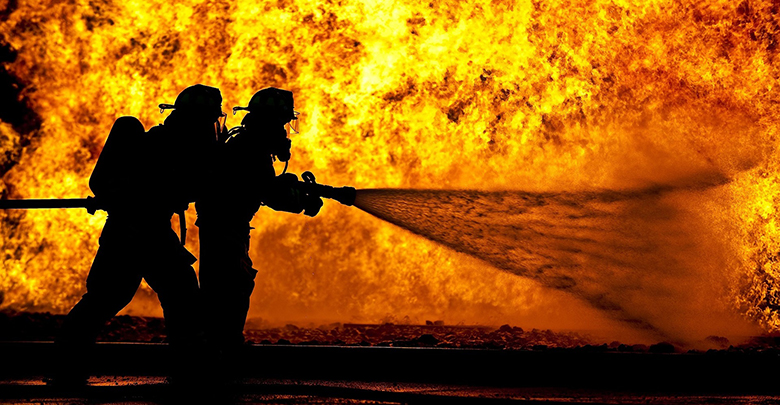 Firefighters silhouetted against fire